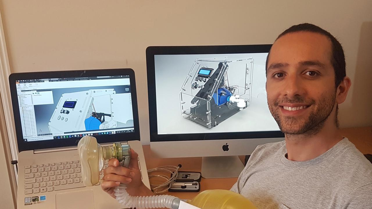 Inventor Ignacio Diaz Katalinic shows the two latest computer models of the ventilator. He is holding the first prototype of the machine made with a Oxy Viva pump donated by Yamba Surf Life Saving Club.