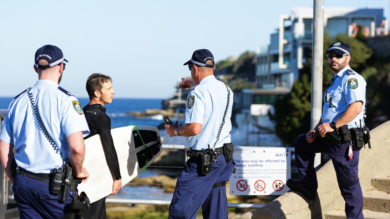 Police speak to a surfer at Bondi — a scene alien to South Australians who have enjoyed less rigid rules. Picture: Gaye Gerard/News Corp