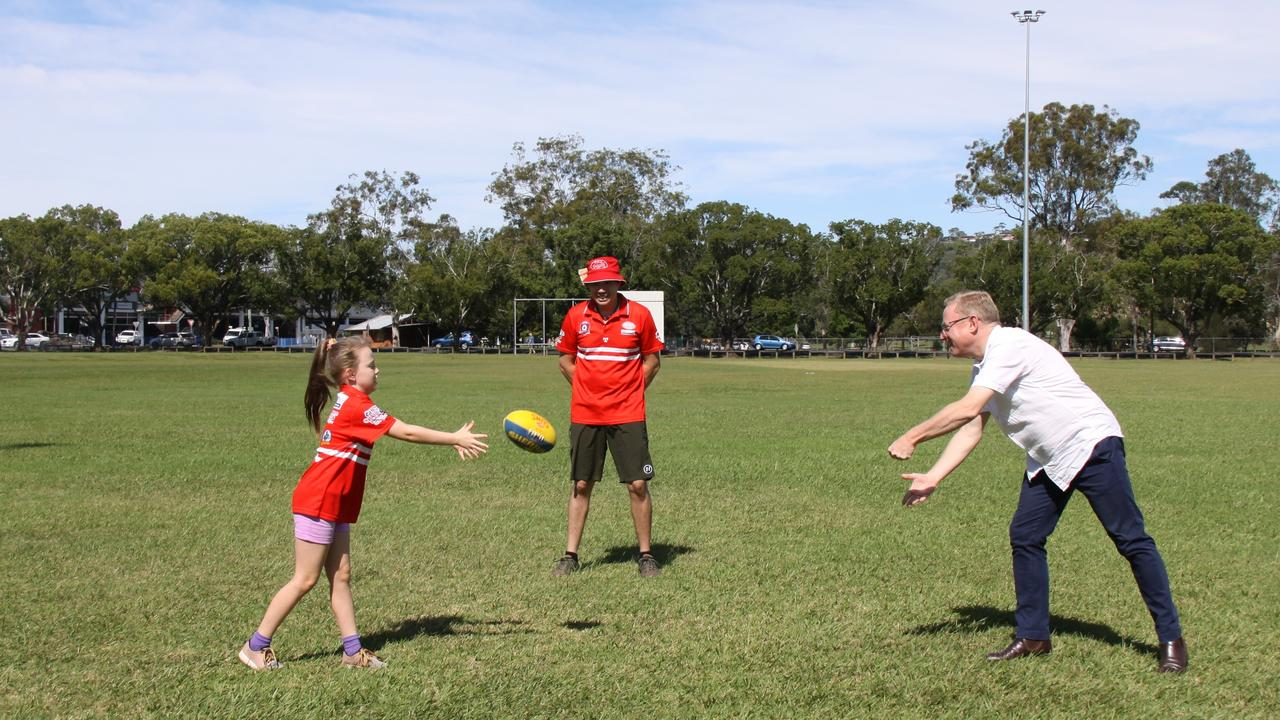 OVAL UPGRADE: Lismore Swans Junior AFL player Katrina McQuilty shows Ben Franklin how to handball as her father Nick looks on. Franklin was there to announce a $115,000 fencing upgrade for Mortimer Oval.