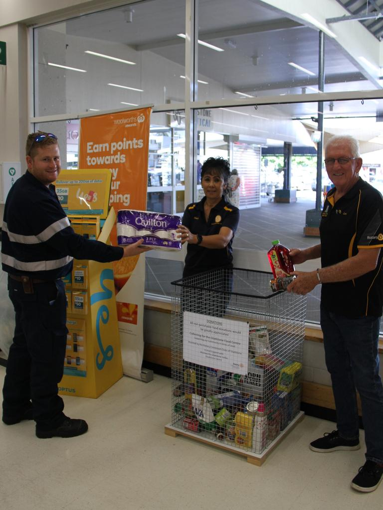 Janri Potgieter of Gladstone generously donates toilet paper to Rotarians Cheryl Royal-Scott and Len Smith for the Gladstone Combined Rotary Clubs Gladstone Food Centre donation drive.