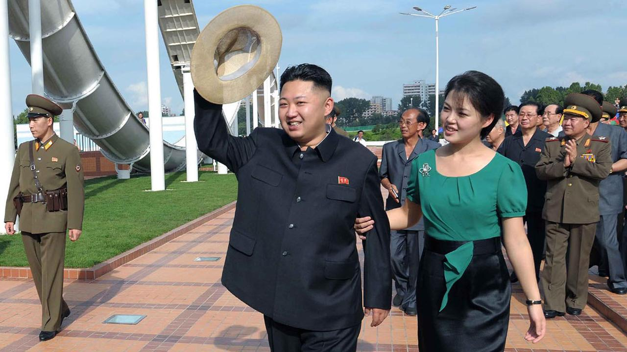 Kim Jong-n, centre, accompanied by his wife Ri Sol Ju, right, waves to the crowd as they inspect the Rungna People's Pleasure Ground in Pyongyang. Korean Central News Agency via Korea News Service