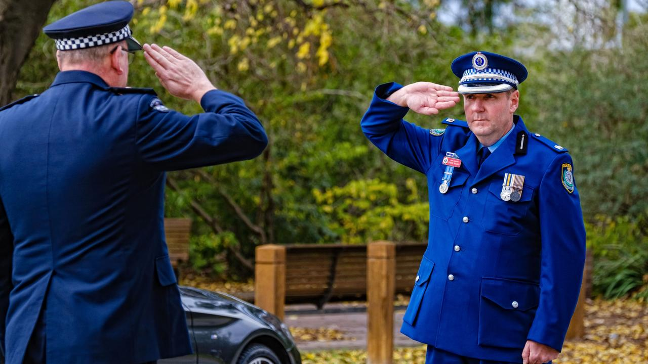The police chiefs ' solemn salute. Picture: AAP Image/Simon Dallinger