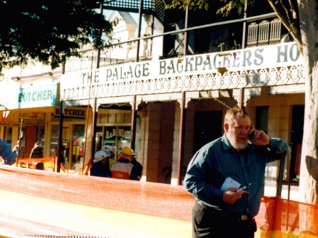 Bill Trevor, then Isis Shire Mayor, outside the burnt-out building in 2000