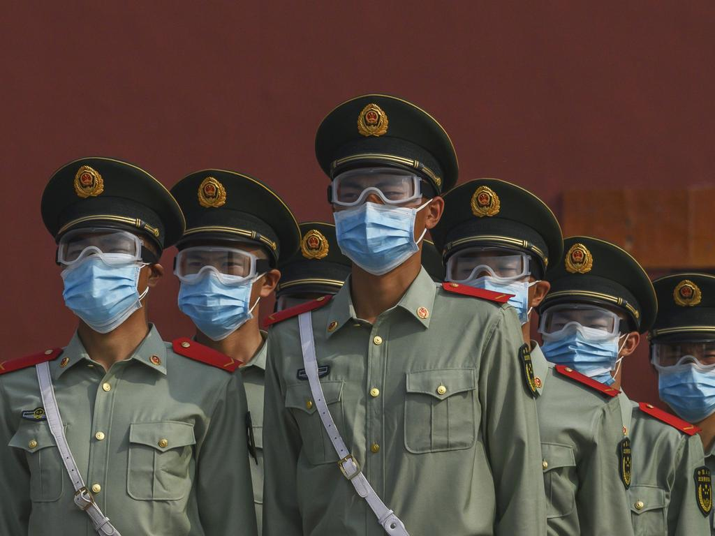 Chinese paramilitary police wear protective masks as they guard the entrance to the Forbidden City as it reopened to limited visitors for the May holiday. Picture: Getty Images