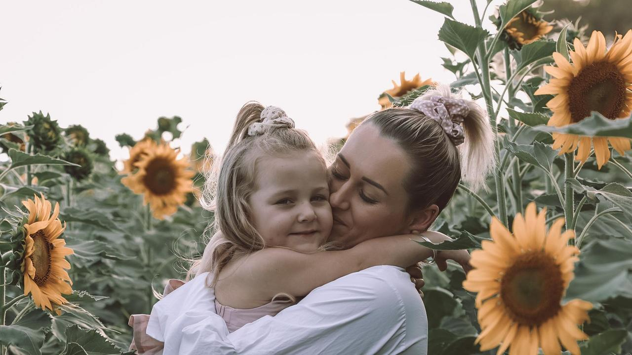 Larissa McIntosh and daughter Kenzie Florence share a moment at the Alton Downs sunflower patch which has brightened the community's spirit in a time of need.