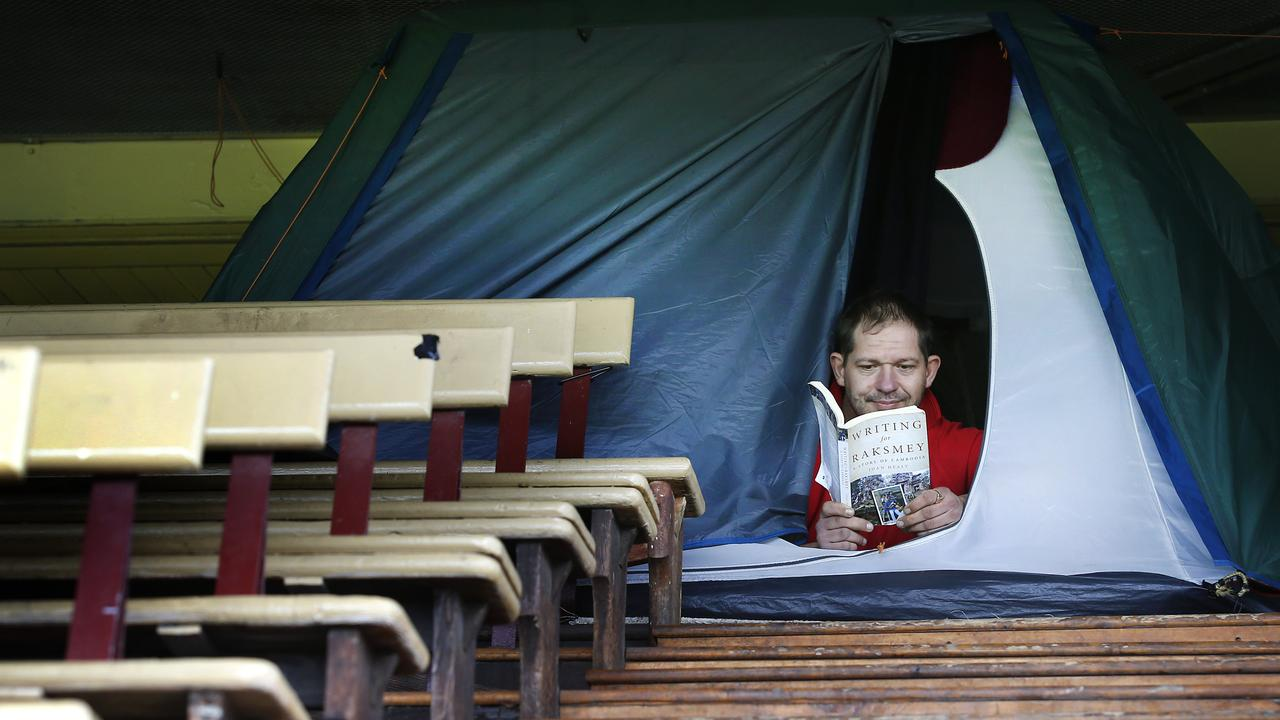 Homeless man Mitch Turner pictured reading a book in his tent last year. Picture: David Caird