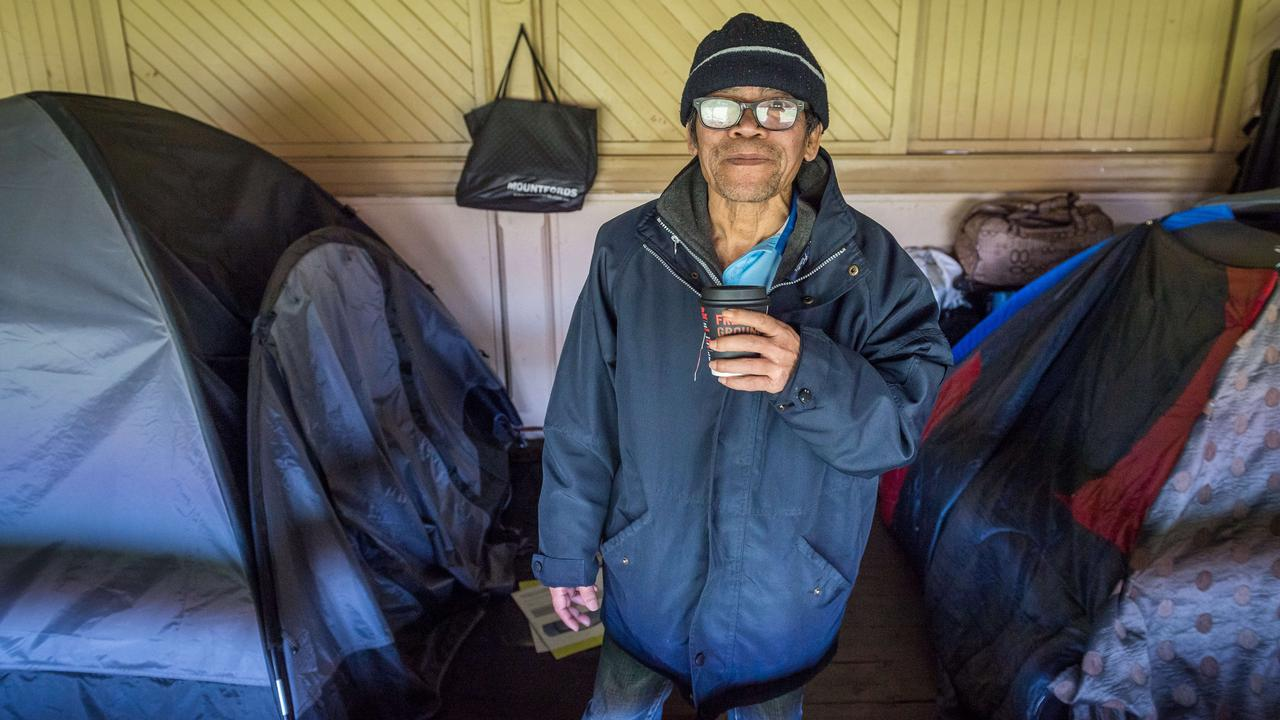 Squatter Dinh stands next to his tent in the Brunswick St Oval grandstand. Picture: Jake Nowakowski