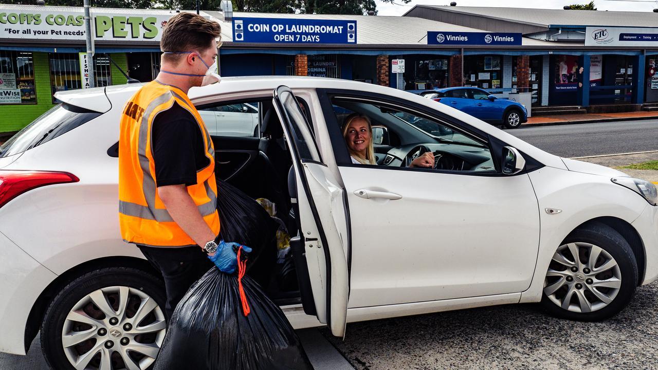 Toormina Hotel staff member Jake Smythe taking Vinnies donations from Ashlee Brindley.