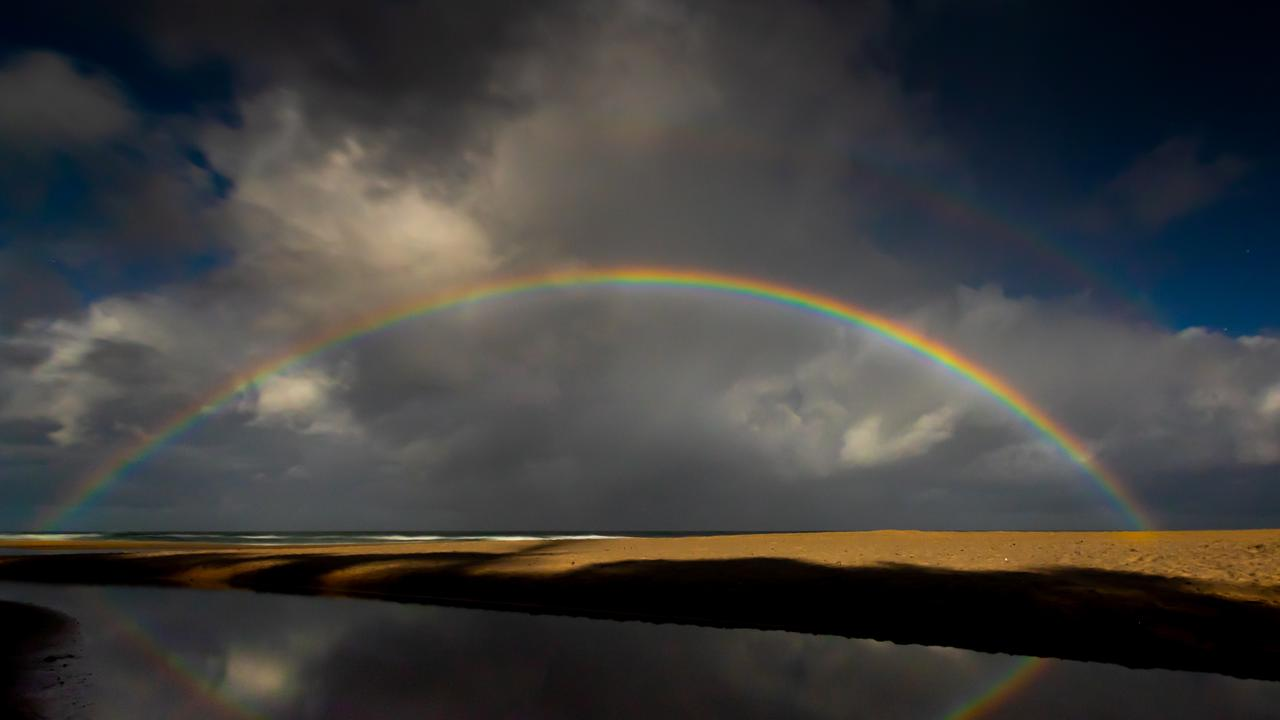 Photographer Ian Waldie caught rare photos of a Moonbow over Sunshine Beach in the early hours of Thursday morning.