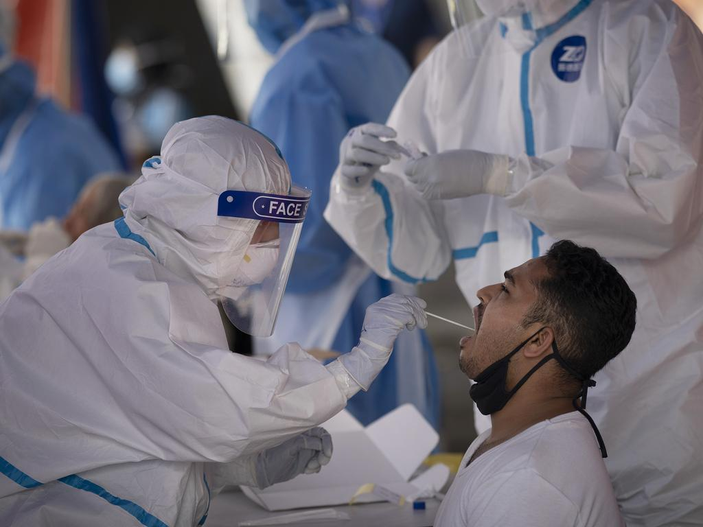 A health worker tests someone for coronavirus at a wet market in Malaysia. Picture: AP Photo/Vincent Thian.