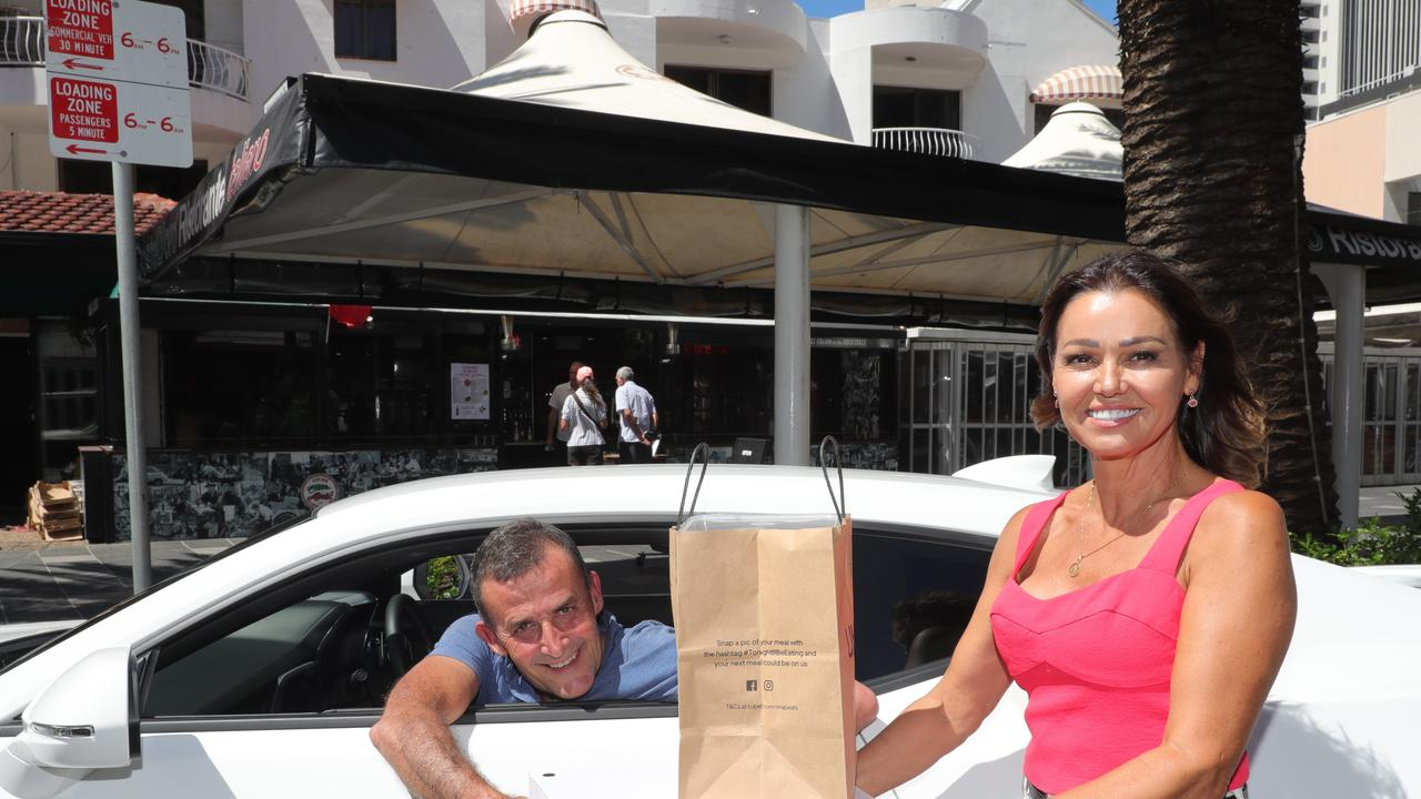 Surfers Paradise Italian favourite Costa D'Oro is offering takeaway - but co-owner Nuccia Fusco - handing takeaway over to driver Darren Graham - said a Government customer limit of 10 for the planned May 16 reopening is unworkable. Picture Glenn Hampson