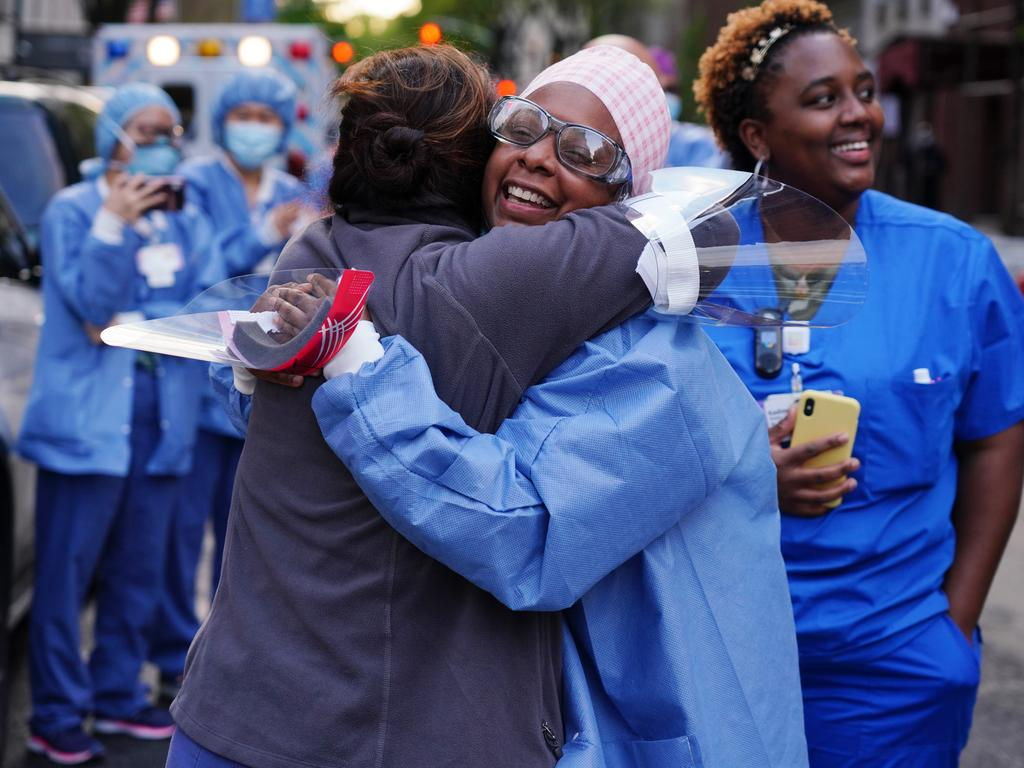 Medical workers from Lenox Hill Hospital in New York hug while people show gratitude as part of the nightly #ClapBecauseWeCare. Picture: Getty Images