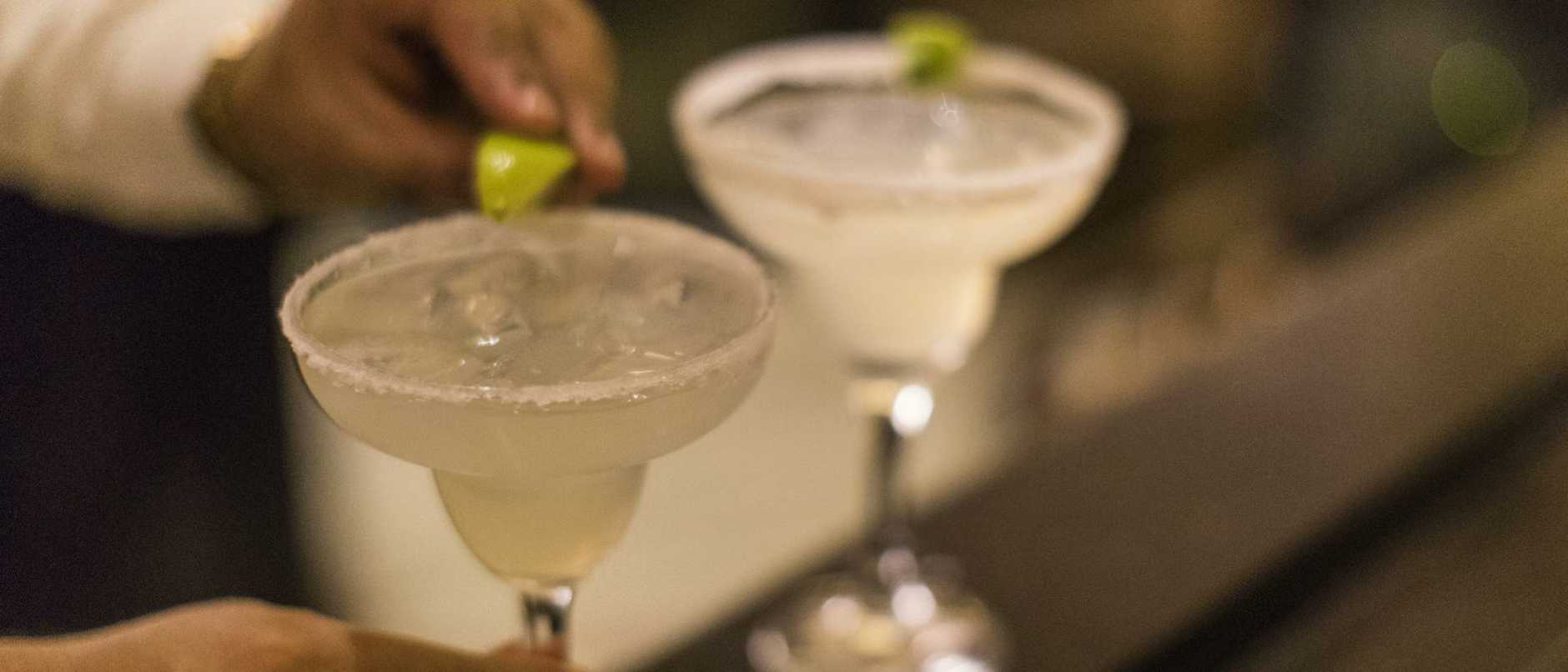 Close-up of an unrecognizable Panamanian bartender putting the final touch on a margarita cocktail by placing a lime wedge on the glass rim.