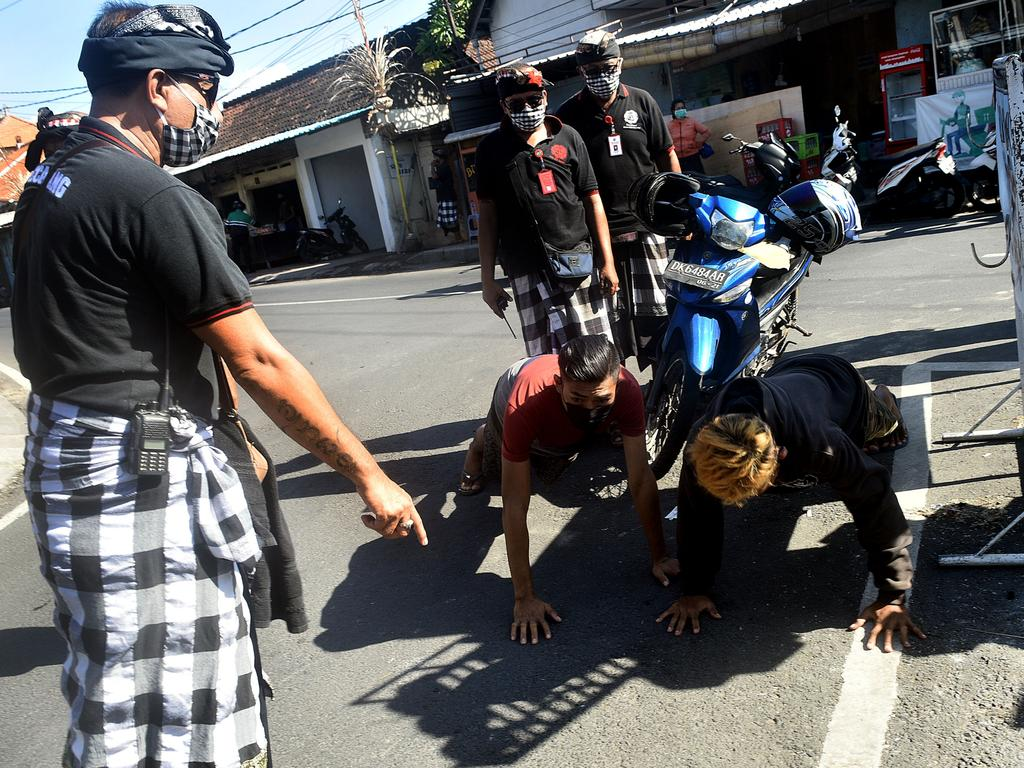 Bali traditional security Pecalang punish riders not wearing face masks with 20 push-ups in Sanur, Bali. Picture. Yuda