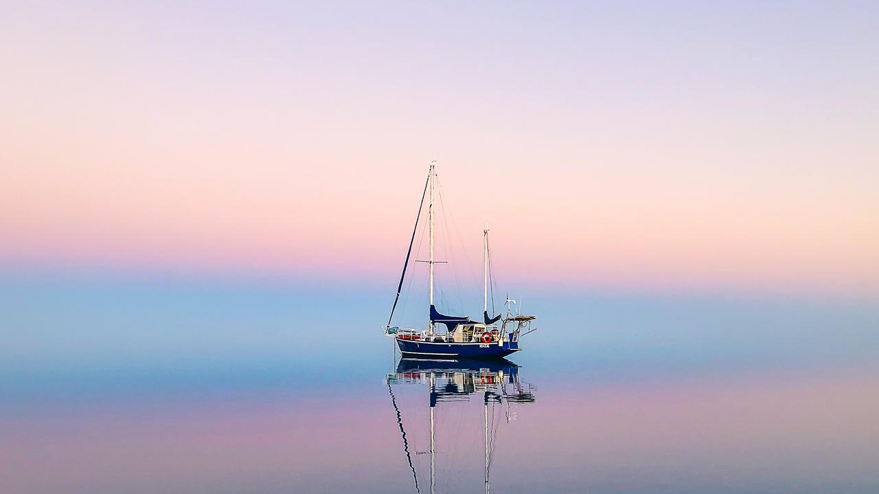 Morningside at anchor at Hardy Lagoon, on the Great Barrier Reef. A one in a million moments where all the elements come together to create a stunning, almost eerie sunset. The result of no wind, clear skies and just enough haze to bring the moment to life.