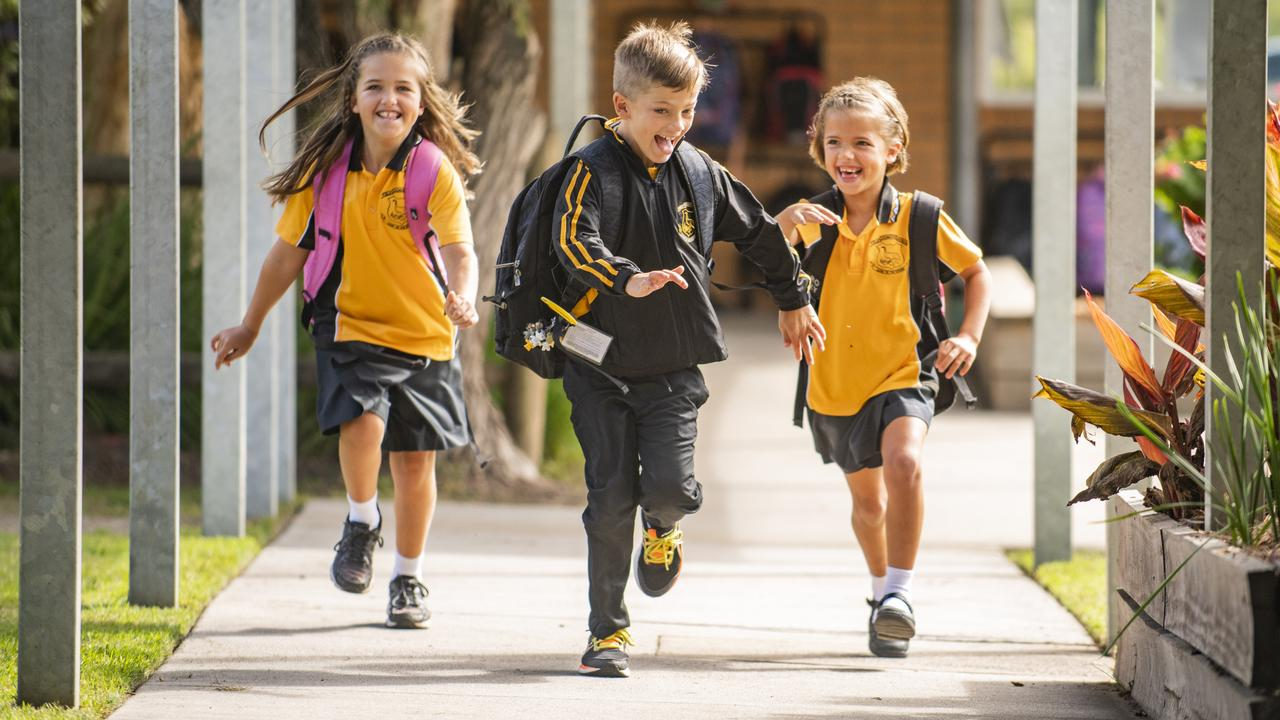 Lucy, 9, Isaac, 7 and Annabelle Smith, 6 show their excitement at being back at Gulmarrad Public School to see their friends. Photo: Adam Hourigan