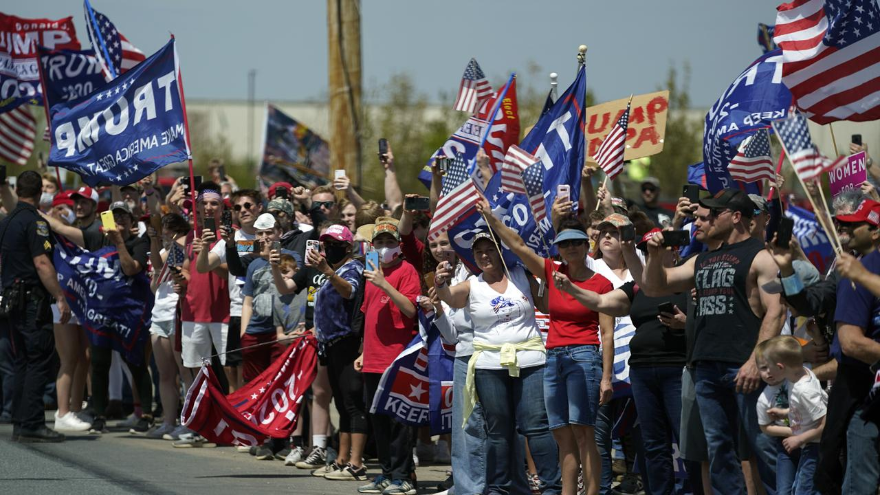 A crowd of supporters looking on as Mr Trump's motorcade passed yesterday. Great social distancing there, guys. Picture: Evan Vucci/AP