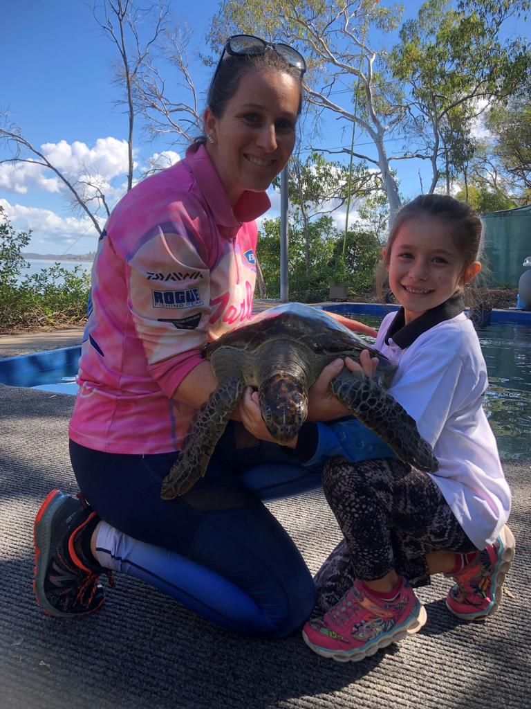 Quoin Island Volunteer Shay Thetford with daughter Amarni, 7, holding a turtle they're about to weigh.