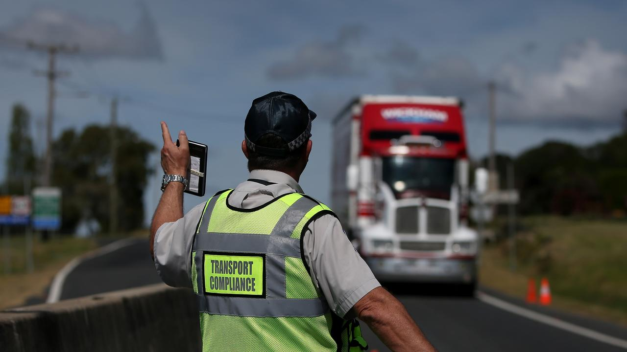 NO DIFFERENCE: A Queensland Transport Inspector signals to a delivery truck approaching the Wallangarra border.