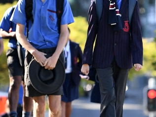 School students, one wearing a surgical mask, arrive for the first day of face-to-face schooling in Brisbane, Monday, May 11, 2020. Students across Queensland in kindergarten, prep and years one, 11 and 12 will return to the classroom for the first time in weeks after a period of learning from home due to the COVID-19 coronavirus pandemic. (AAP Image/Dan Peled) NO ARCHIVING