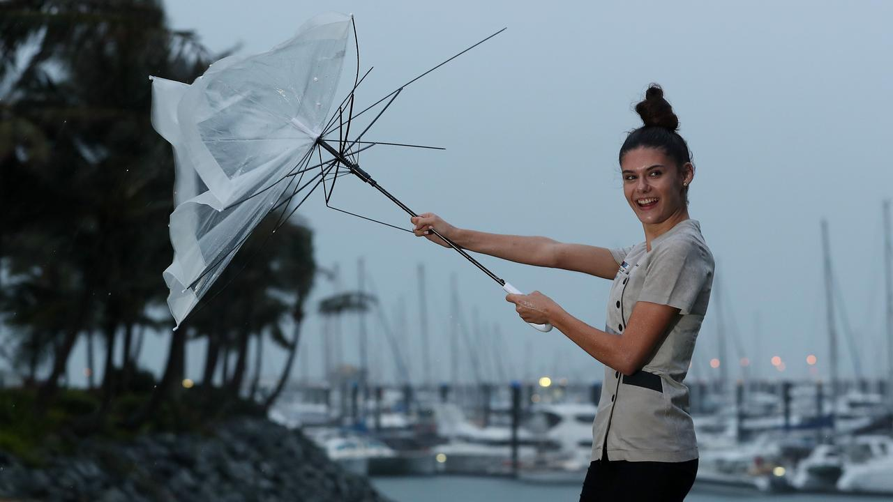 Danielle Vella struggles with her umbrella in Mackay as the wet weather moves in. Picture: Peter Wallis