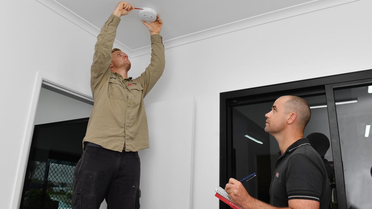Smoke Alarms Mackay Electrician Jackson McCormack fits a smoke alarm while Smoke Alarms Mackay owner Dirk Widdowson watches on. Picture. Tony Martin