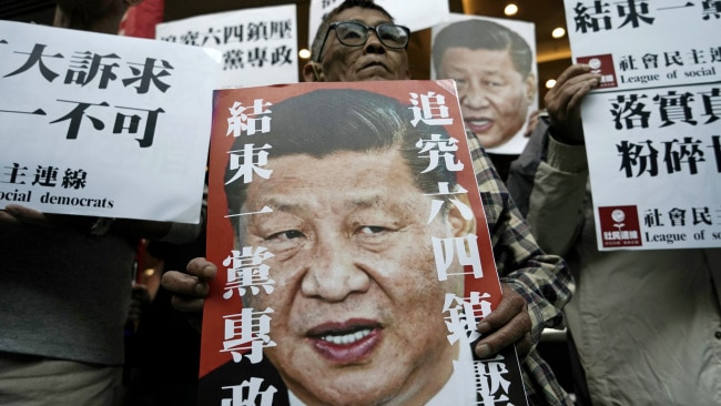 Pro-democracy activists hold up placards of Chinese President Xi Jinping with slogans including