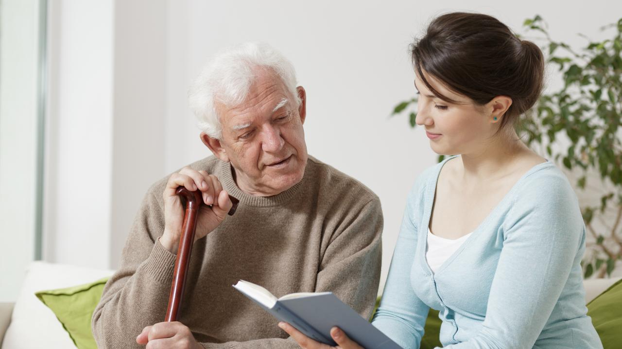 Quest, Active Living, June 2017 – Home Care Assistance. Image of young carer reading book to senior man