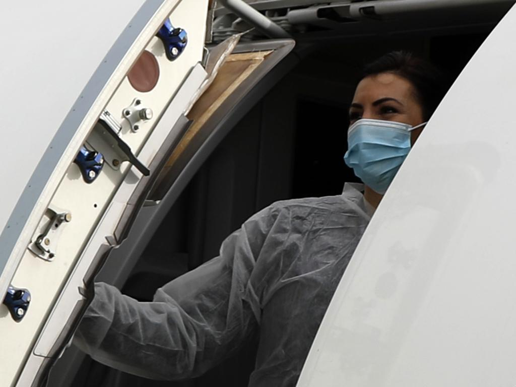 An air hostess closes the aircraft door after boarding is completed. Picture: AP