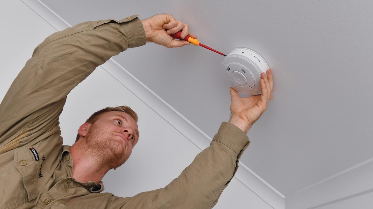 Smoke Alarm Mackay electrician Jackson McCormack fits a smoke alarm. Picture: Tony Martin