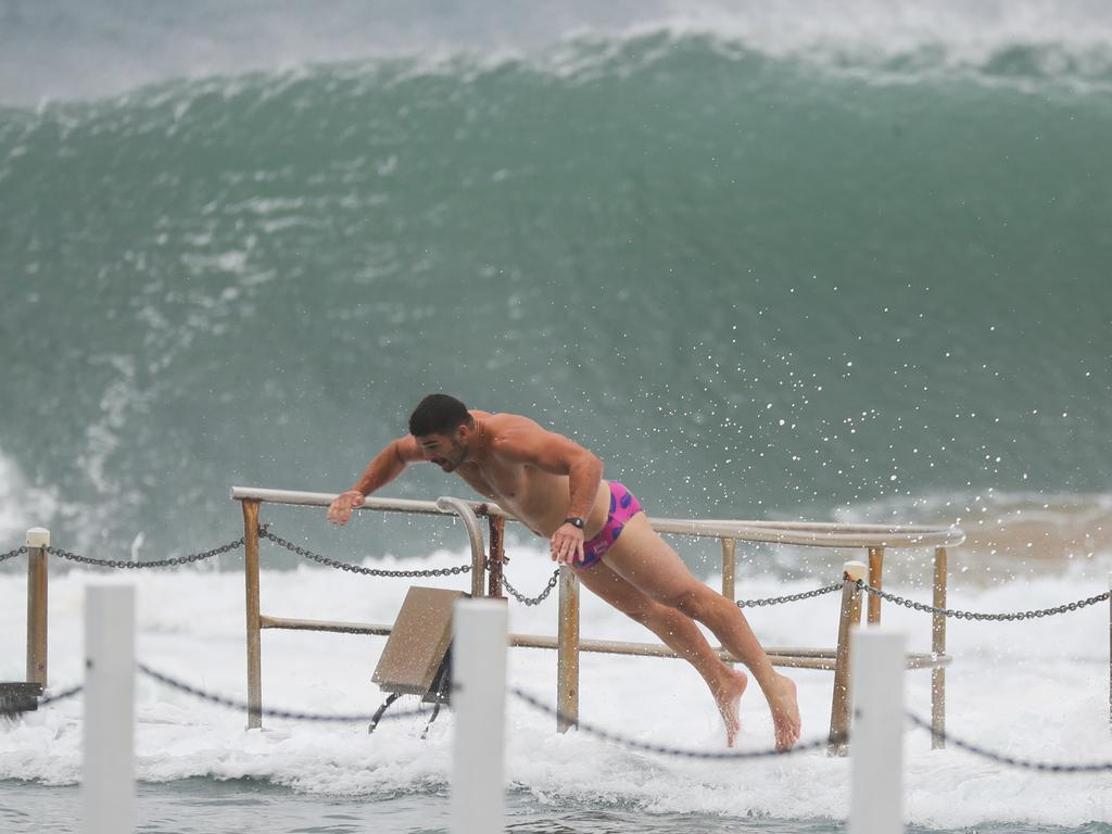 A swimmer dives into choppy waters at North Narrabeen as the swell turns the ocean pool into a washing machine. Picture John Grainger