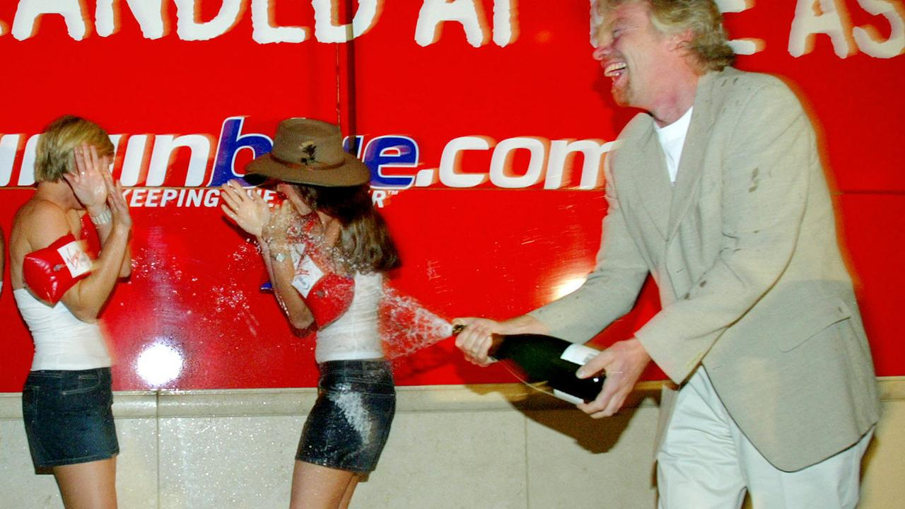 DECEMBER 8, 2003: British tycoon Richard Branson sprays young girls with bubbly at Australian Stock Exchange as discount airline Virgin Blue is floated on ASX in Sydney, 08/12/03.