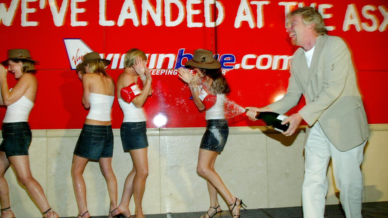 Virgin Group founder Richard Branson sprays young girls with bubbly at the ASX float of Virgin Blue in December 2003.