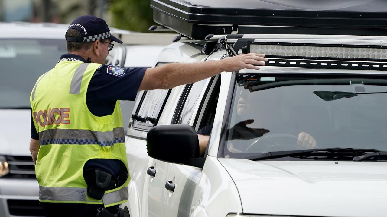 A Queensland police officer gestures for a motorist to pull over at a checkpoint at Coolangatta on the Queensland-New South Wales border last Friday. Picture: AAP Image/Dave Hunt