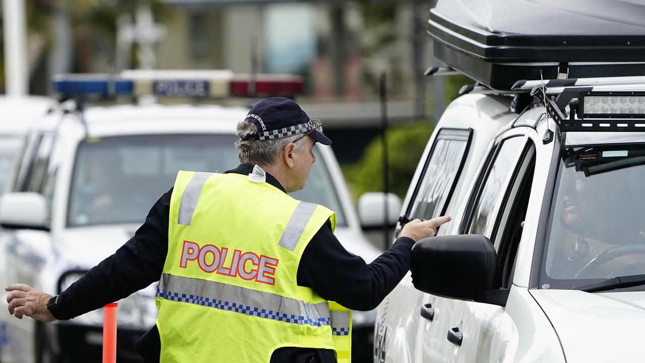 A Queensland police officer speaks with a motorist at a checkpoint at Coolangatta on the Queensland-New South Wales border. (AAP Image/Dave Hunt)