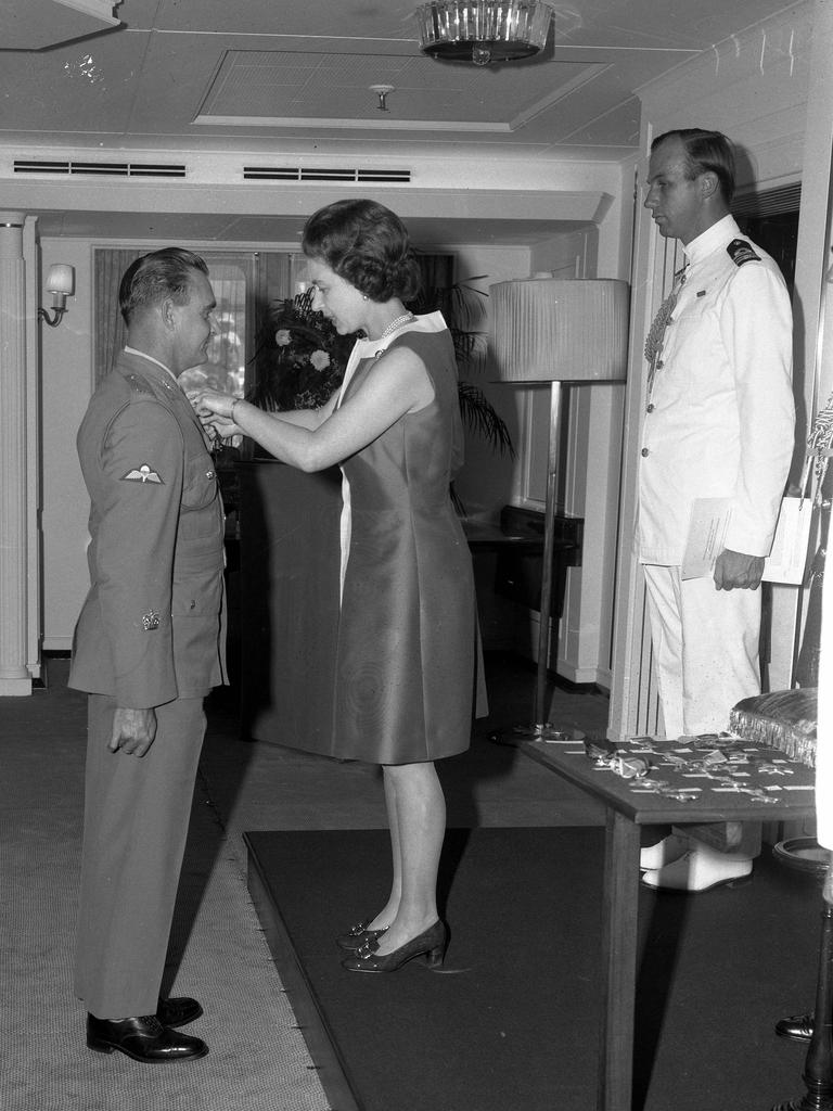 Warrant Officer Keith Payne being presented with the Victoria Cross medal for bravery by the Queen on board the Royal Yacht Britannia in Brisbane. Picture: The Courier-Mail Photo Archive.
