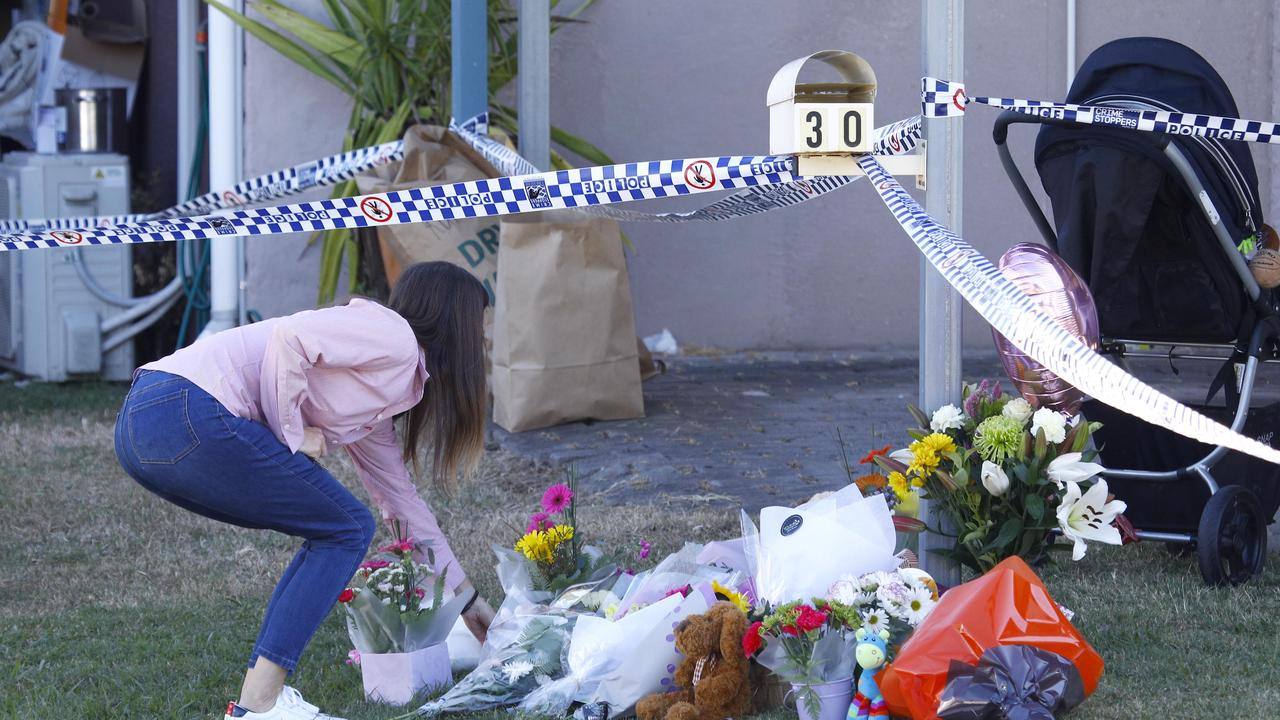 Members of the public leave flowers outside the home where the body of Willow Dunn was found. Picture: Tertius Pickard