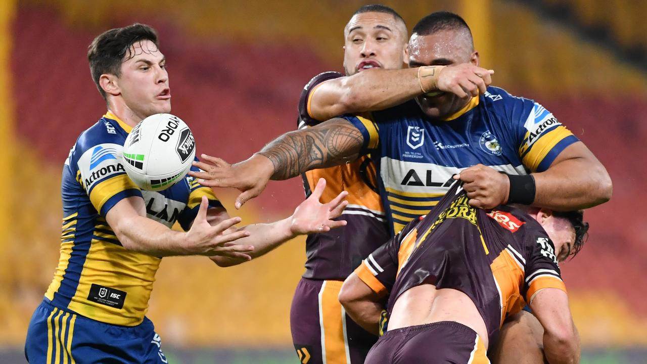 Parramatta prop Junior Paulo fires out a blind pass as halfback Mitchell Moses comes in to assist. Picture: AAP Image/Darren England