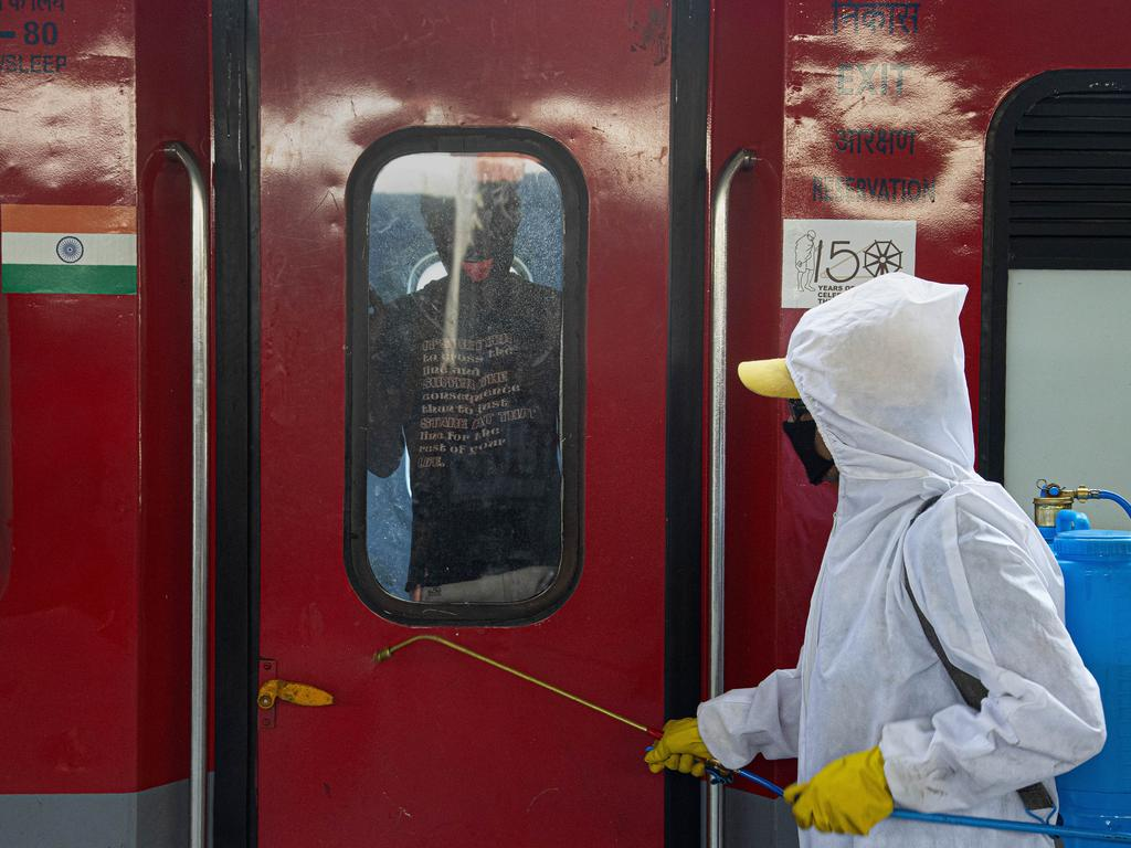 A railway worker disinfects a train carrying migrant workers to their home states, at a railway station in Gauhati, India. Picture: AP