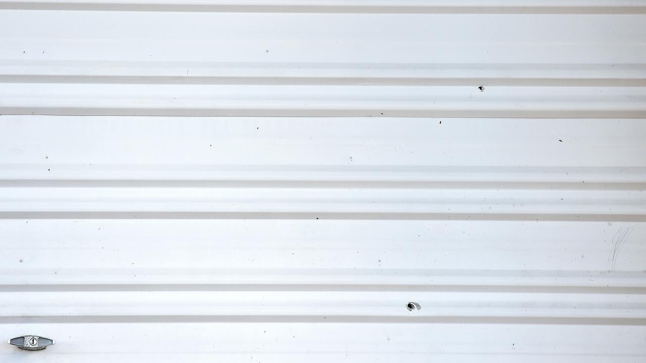 Holes in a garage door after a shooting in Gould Street, Kirwan. Picture: Shae Beplate.