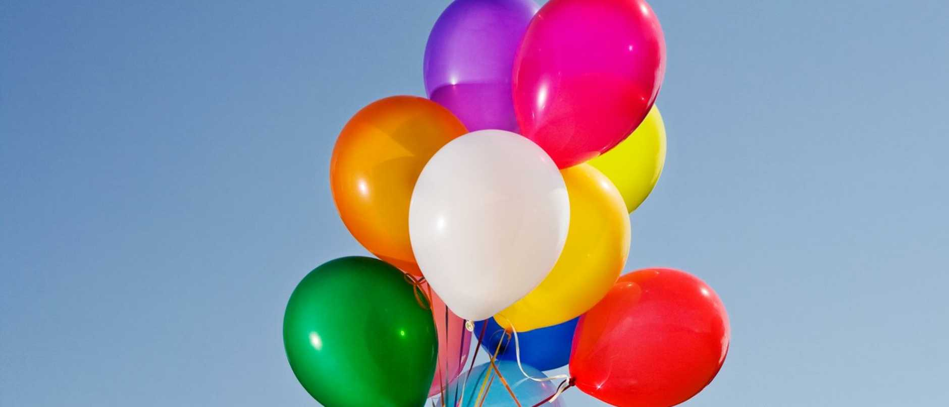 Little blond girl with multicolored balloons