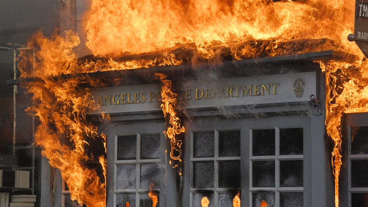 A Los Angeles Police Department kiosk was set ablaze in a riot. Picture: AP Photo/Mark J. Terrill