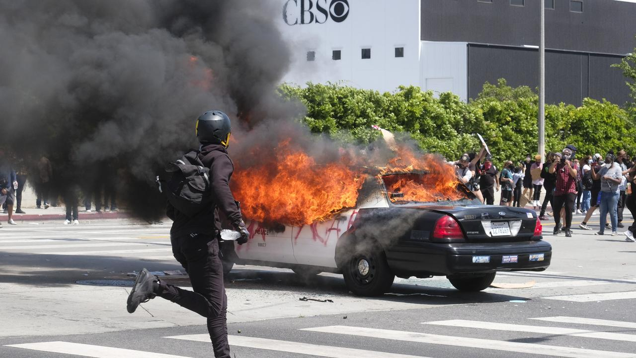 A person runs while a police vehicle is burning during a protest over the death of George Floyd in Los Angeles. Picture: AP Photo/Ringo HW Chiu