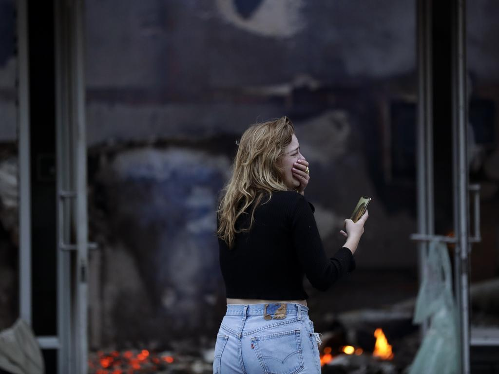 A woman cries as she watches a building burn after a protest over the death of George Floyd in La Mesa, Calif. Picture: Gregory Bull
