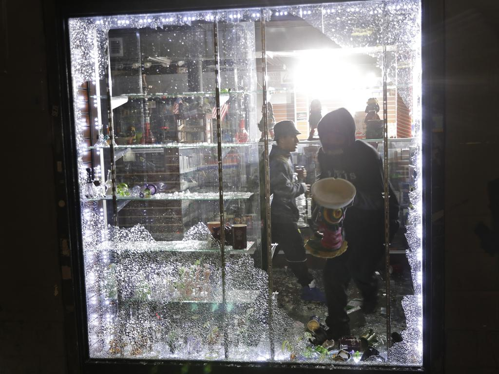 Looters carry goods from a smoke shop through a broken window in New York. Picture: AP