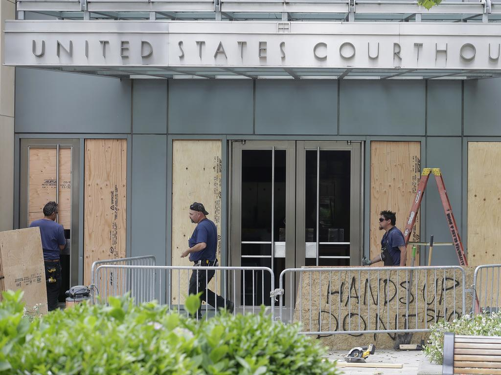 People work outside a damaged courthouse. Picture: Jeff Chiu/AP