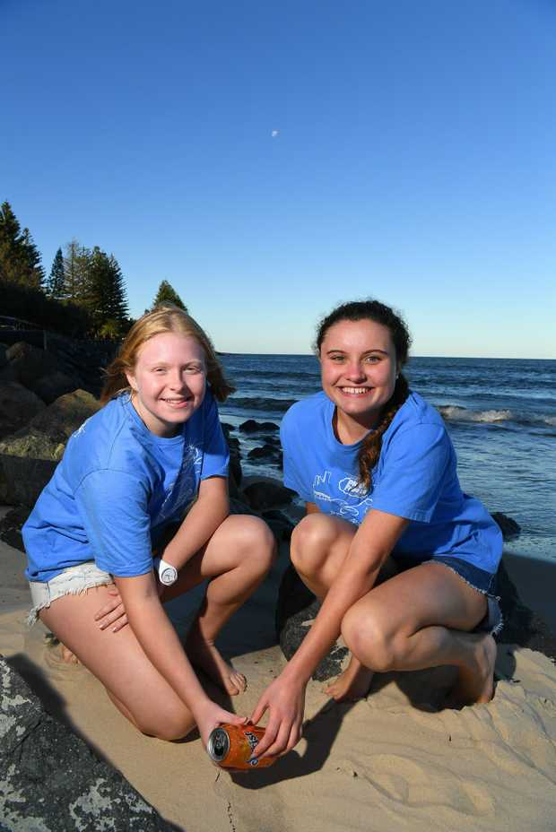 Image for sale: Debbies daughter Poppy, 15, and her friend are setting up a Seaside Scavenge for Caloundra. Its a festive beachside market where you can swap trash (litter from a beach cleanup) for treasure (secondhand clothes etc). itll go ahead in September, covid-permitting. Poppy Ives,15 and Jazmin Simmons,16, picking up rubbish on the beach.