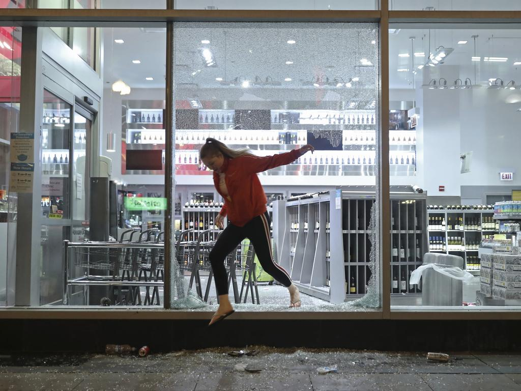 A woman jumps out of a Walgreens store empty-handed in Chicago, after seeing police officers nearby. Picture: John J. Kim/Chicago Tribune via AP