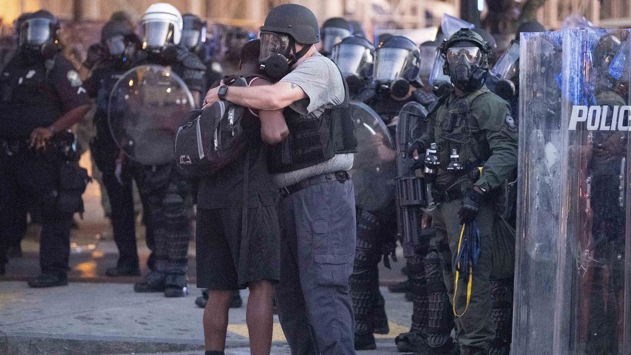 A police officer embraces a protester who helped disperse a crowd of people in Atlanta. Picture: John Bazemore/AP