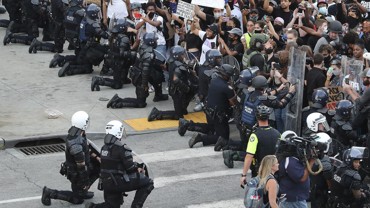 Police have taken a knee at protests from coast to coast. Picture: Curtis Compton/Atlanta Journal-Constitution via AP)